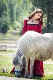 深色的女孩和马 免版税库存照片