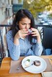 深色的女孩喝茶用在咖啡馆的点心 免版税库存照片