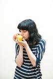 深色的女孩嗅到苹果和桔子在她的手上 免版税库存图片