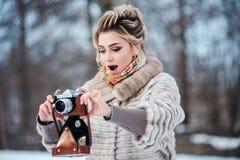 深色的女孩在冬天雪公园站立,拿着一台老影片照相机并且调查距离 免版税库存图片
