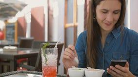 深色的女孩在咖啡馆使用巧妙的电话,当坐外面,吃冰淇凌时 4k, 免版税库存图片