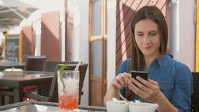 深色的女孩在咖啡馆使用巧妙的电话,当坐外面,喝和享受从秸杆管时的一个冷饮 4k, 免版税库存照片