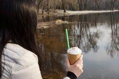 深色的女孩在她的手上的拿着一块玻璃用在水的咖啡在水附近 图库摄影