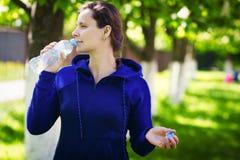 深色的女孩在绿色夏天公园喝从瓶的饮用水 健康生活方式 饮用的净水概念 图库摄影