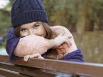 深色的女孩坐一条长凳在秋天 库存照片