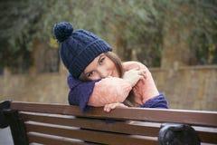 深色的女孩坐一条长凳在秋天 图库摄影
