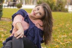 深色的女孩坐草在秋天 图库摄影