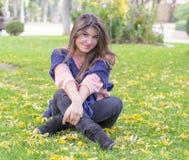 深色的女孩坐草在秋天 免版税库存照片