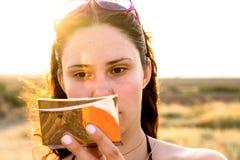 年轻深色的女孩的面孔有化妆镜子的在明亮的太阳发出光线 免版税库存照片