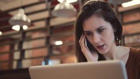 年轻深色的女孩研究膝上型计算机和谈话在咖啡馆的电话 股票视频