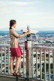 年轻深色的女孩观察与的都市风景旅游观光的双筒望远镜 免版税图库摄影