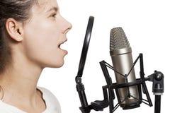 深色的女孩记录声音到演播室话筒 少妇在演播室有被隔绝的蜘蛛的电容传声器唱歌 免版税库存照片