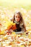 深色的女孩金黄叶子 免版税库存图片
