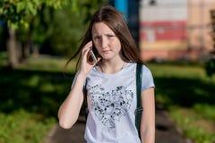 深色的女孩 在夏天在新鲜空气的公园 他在电话谈话 情感一次严肃的交谈 免版税库存照片
