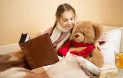 深色的女孩画象讲故事对玩具熊在床 免版税库存图片