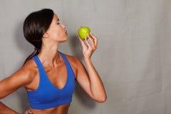 深色的女性举行的和亲吻的苹果 免版税库存照片
