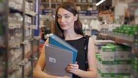 年轻深色的妇女、学生、实习生或者雇员,微笑,当选择正确的书或文件从办公室时 股票录像