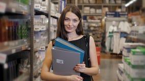 年轻深色的妇女、学生、实习生或者雇员,微笑,当选择正确的书或文件从办公室时 免版税库存照片