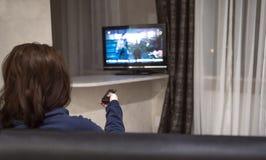 深色的妇女交换电视频道,当在家坐长沙发,背面图时 免版税库存照片