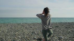 深色的妇女伸手,站立在海岸的一条腿,后面看法 影视素材
