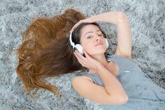 年轻深色的妇女听的音乐,当放置在地毯时 免版税库存照片