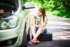 年轻深色的妇女在一辆银色汽车附近坐与一个残破的轮子的路旁 免版税图库摄影