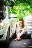 年轻深色的妇女在一辆银色汽车附近坐与一个残破的轮子的路旁 库存照片