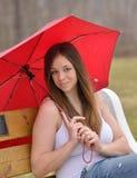 深色的妇女在伞下在雨中 免版税库存图片