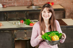 深色的妇女在厨房拿着有新鲜蔬菜的一个碗并且看照相机并且微笑 健康的食物 图库摄影
