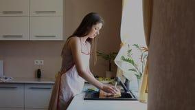 深色的妇女在厨房里洗肮脏的盘子 股票录像