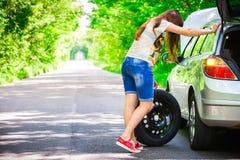 年轻深色的妇女在路旁的一辆银色汽车附近站立与一个残破的轮子 图库摄影