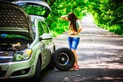 年轻深色的妇女在路旁的一辆银色汽车附近站立与一个残破的轮子 库存照片
