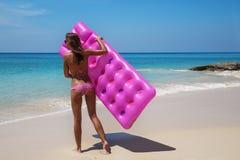 深色的妇女太阳镜晒日光浴与在热带海滩的气垫 库存图片