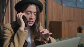 深色的妇女由手机执行交涉,坐在街道咖啡馆 影视素材