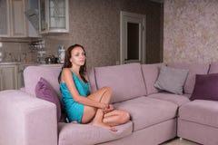 年轻深色的妇女观看的电视在家 免版税库存图片