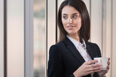 深色的妇女饮用的咖啡在办公室 免版税图库摄影