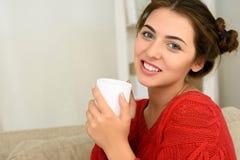 年轻深色的妇女饮用的咖啡或茶 免版税库存图片