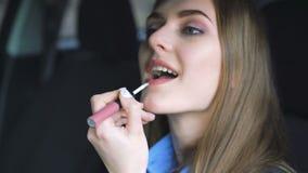 年轻深色的妇女绘她的在汽车的嘴唇 4K 股票录像