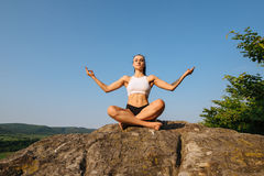 深色的妇女画象有强健的身体实践的瑜伽的在岩石 背景蓝天 和谐和放松 库存图片
