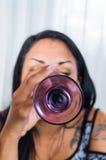 深色的特写镜头举的玻璃和喝,底下饰面照相机 库存图片