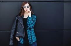 深色的站立户外在城市的女孩佩带的皮夹克画象对黑都市墙壁 免版税库存照片