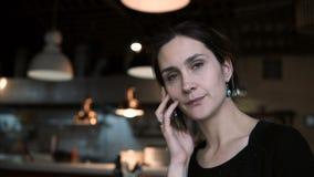 深色的美丽的妇女坐在咖啡馆和谈话在有朋友的手机 使用智能手机的可爱的女性 股票录像