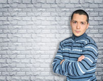 年轻深色的身分对有横渡的胳膊的墙壁 免版税库存照片