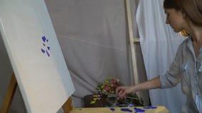 深色的画家做第一污迹蓝色油漆在站立一艘白色的废船在一个木画架并且调直 股票录像