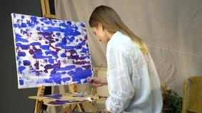 深色的画家在帆布前坐并且混合在一个木调色板的油漆 股票录像