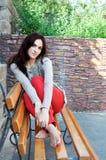 深色头发的女孩坐长凳 免版税库存照片