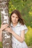 年轻深色头发的妇女拥抱桦树画象  库存图片