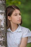 年轻深色头发的妇女拥抱桦树画象  免版税库存图片