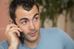 年轻深色头发的男性模型谈话在他的手机 免版税图库摄影