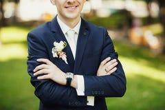 深蓝套装的时髦的新郎有钮扣眼上插的花的 免版税库存图片